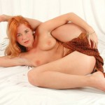 Nude red-haired contortionist in leopard bodysuit shows off her lissome body